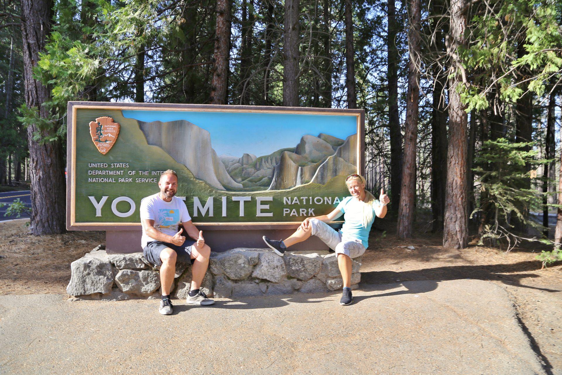 Einfahrtsschild am Westeingang des Yosemite Nationalpark - Baumstämme, Blondine, Einfahrt, Einfahrtsschild, Kalifornien, Personen, Portrait, Porträt, Schild, Welcome-Schild, Yosemite National Park - HOFBAUER-HOFMANN Sofia, WEISSINGER Andreas - (Sequoia, Groveland, California, Vereinigte Staaten)