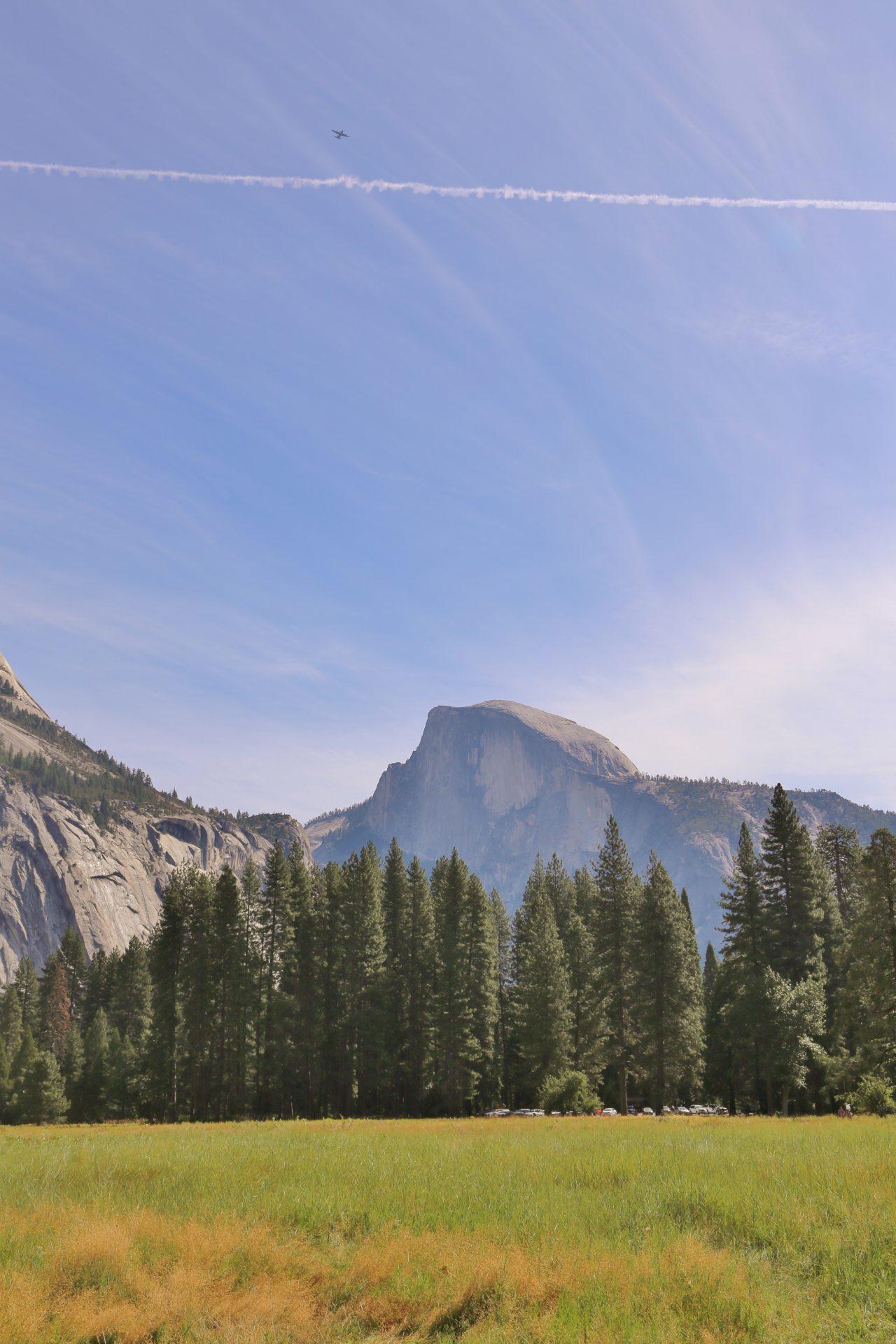 Half Dome in Aktion - Aussicht, Bäume, Berg, Fernsicht, Flugzeug, Half Dome, Himmel, Kalifornien, Kondensstreifen, Landschaft, Natur, Panorama, Wiese, Wolken, Yosemite National Park - (Yosemite Village, Yosemite National Park, California, Vereinigte Staaten)