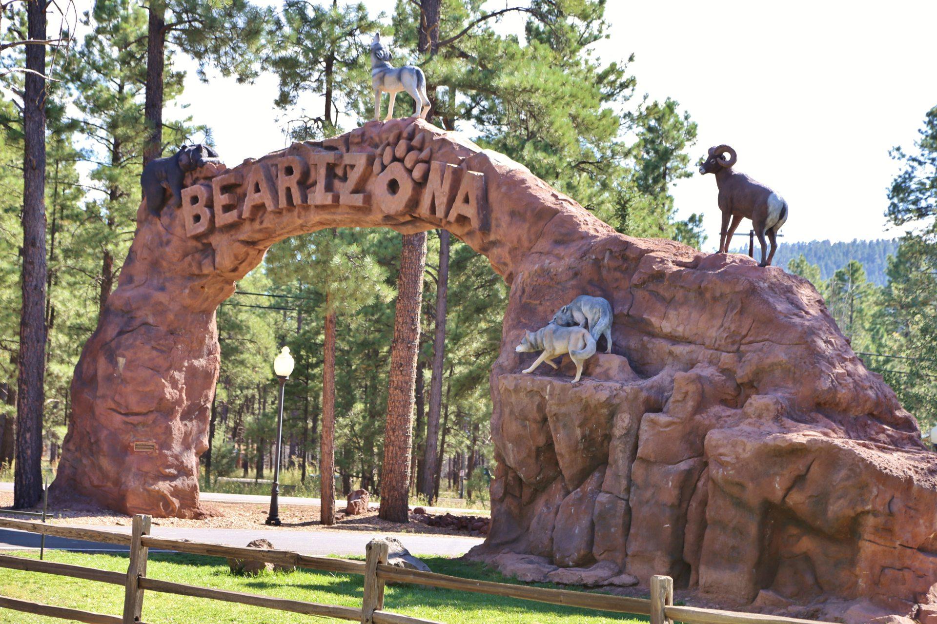 Bearizona Tiererlebnispark - Arch, Arizona, Bäume, Bearizona, Einfahrtsbogen, Einfahrtsschild, Eingang, Himmel, Tiere, Tierpark, Welcome-Schild, Zaun - (Kaibab Mobile Home Park, Williams, Arizona, Vereinigte Staaten)