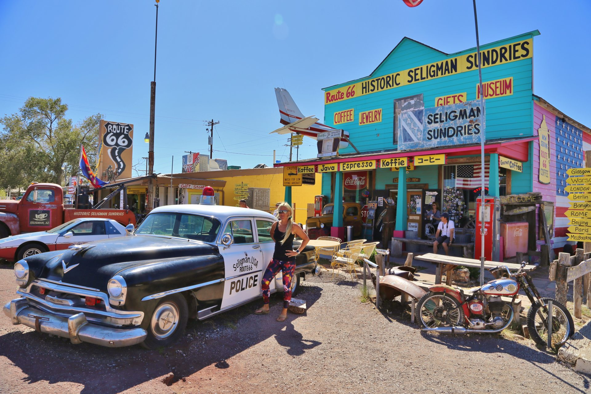 Von dem Polizeischlitten lass auch ich mich abführen - Arizona, Auto, Beschilderung, Blondine, Fahrzeug, Gebäude, Himmel, KFZ, Motorrad, Personen, Polizei, Route 66, Schilder, Seligman, Souvenierladen - HOFBAUER-HOFMANN Sofia - (Seligman, Arizona, Vereinigte Staaten)