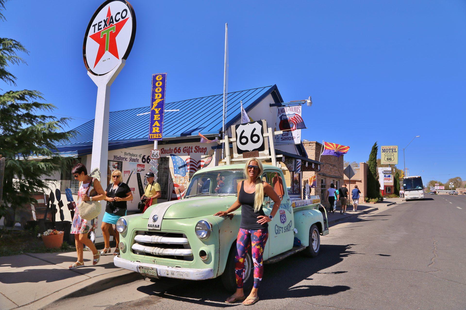 Route 66 und was davon noch blieb - Angel and Vilma Delgadillos Gift Shop, Arizona, Auto, Beschilderung, Blondine, Dodge, Fahrzeug, Gebäude, Goodyear Tires, Himmel, KFZ, Mast, Oldtimer, Personen, Portrait, Porträt, Route 66, Schild, Schilder, Seligman, Souvenierladen, Strasse, Texaco, Werbeschilder - HOFBAUER-HOFMANN Sofia - (Seligman, Arizona, Vereinigte Staaten)