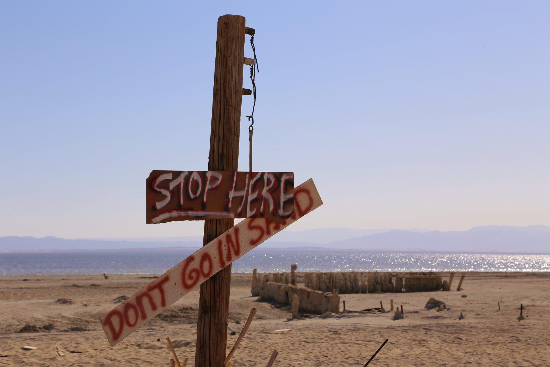 Salton Sea lädt niemanden mehr zum Baden ein - Aussicht, Bombay Beach, Endzeitstimmung, Fernsicht, heruntergekommen, Himmel, Kalifornien, Landschaft, Natur, Panorama, Salton Sea, Schild, STOP HERE, Tafel, verfallen, verkommen, Weltuntergangsstimmung - (Bombay Beach, Niland, California, Vereinigte Staaten)