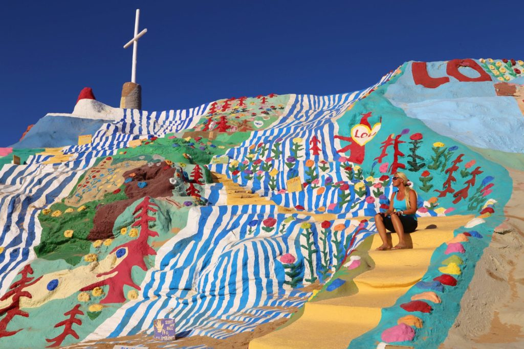 Bunt ist meine Lieblingsfarbe am Salvation Mountain - Attraktion, Berg, Blondine, Bunt, Denkmal, Farben, farbenfroh, Gott liebt alle, Himmel, Kalifornien, Kreativität, Kunst, Kunstinstallation, Kunstwerk, Leonard Knight, Personen, Portrait, Porträt, Salvation Mountain, Sehenswürdigkeit, Slab City - HOFBAUER-HOFMANN Sofia - (Niland, California, Vereinigte Staaten)